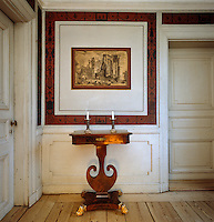 A small table stands beneath an etching which has been pasted to the wall and is surrounded by a frame depicting Pompeian motifs
