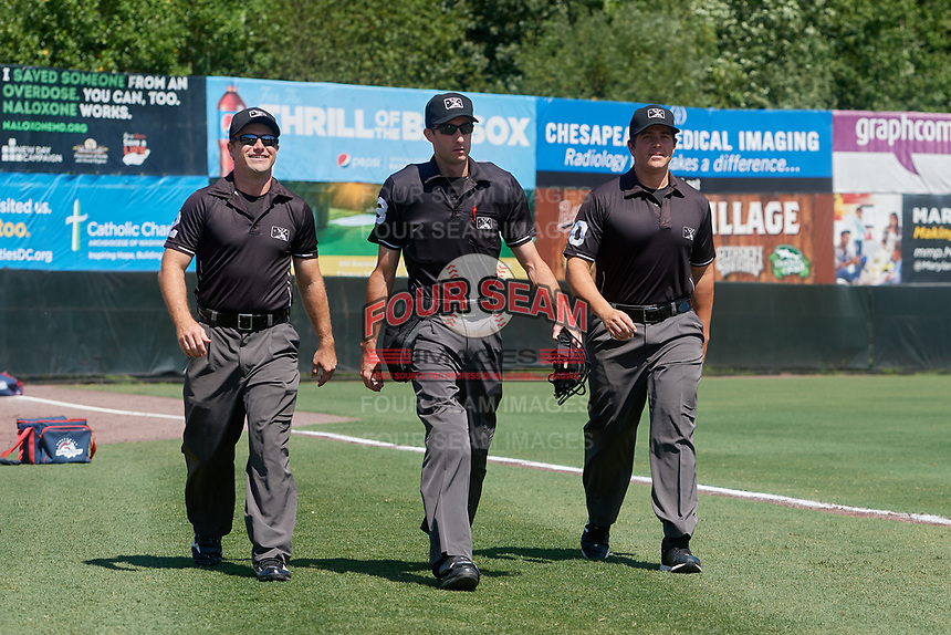 Umpires Tom West, Sean Shafer-Markle, and Mike Savakinas walk to the field before an Eastern League game between the Binghamton Rumble Ponies and Bowie Baysox on August 21, 2019 at Prince George's Stadium in Bowie, Maryland.  Bowie defeated Binghamton 7-6 in ten innings.  (Mike Janes/Four Seam Images)