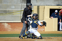 Quinnipiac Bobcats catcher Matthew Oestreicher (20) throws the ball back to his pitcher as home plate umpire Randal Dulin looks on during the game against the Radford Highlanders at David F. Couch Ballpark on March 4, 2017 in Winston-Salem, North Carolina. The Highlanders defeated the Bobcats 4-0. (Brian Westerholt/Four Seam Images)
