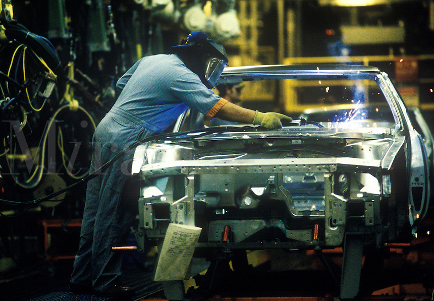 Auto worker spot welds hood of vehicle