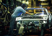Auto worker spot welds hood of vehicle