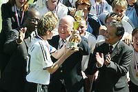 Sepp Blatter, FIFA President, hands Bettina Wiegmann the World Cup trophy after Germany defeates Sweden 2-1.