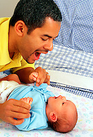 Hispanic father interacts with his baby boy.