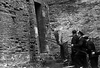"""9 juin 1961. Arrivée des accusés : un homme monte un escalier pour entrer dans la palais de justice (vue de profil), il est suivi par plusieurs policiers. Cliché pris dans le cadre de l'affaire de la """"Tournerie des drogueurs"""" dont le procès s'est ouvert à Toulouse le 5 juin 1961. Observation: Affaire de la """"Tournerie des drogueurs"""" : Procès qui s'est ouvert aux assises de Toulouse le 5 juin 1961, sous la présidence de M. Gervais (conseiller doyen). Sur le banc des accusés se trouvent François Lopez, Raoul Berdier, Marie-Thérèse Davergne (Maïté) et d'autres malfaiteurs toulousains (Camille Ajestron, Henri Oustric, Raymond Peralo, Marcel Filiol, Paul Carrère, Charles Davant et François Borja). Outre les accusations pour association de malfaiteurs, ils comparaissent pour l'assassinat de Jean Lannelongue, propriétaire du Cabaret la Tournerie des Drogueurs (rue des Tourneurs) dans la nuit du 3 au 4 janvier 1959, au cours d'une tentative de racket."""