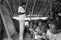 Uganda. West Nile. Adjumani. Public school. Teacher in classroom. Blackboard and pupils sitting on the ground. West Nile sub-region (previously known as West Nile Province and West Nile District) is a region in north-western Uganda. © 1989 Didier Ruef