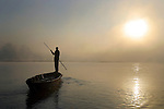 A man navigates his wooden boat across the Rapti River in the Terai region of Nepal. The river is a natural boundary between Chitwan National Park and the village of Sauraha, Nepal.