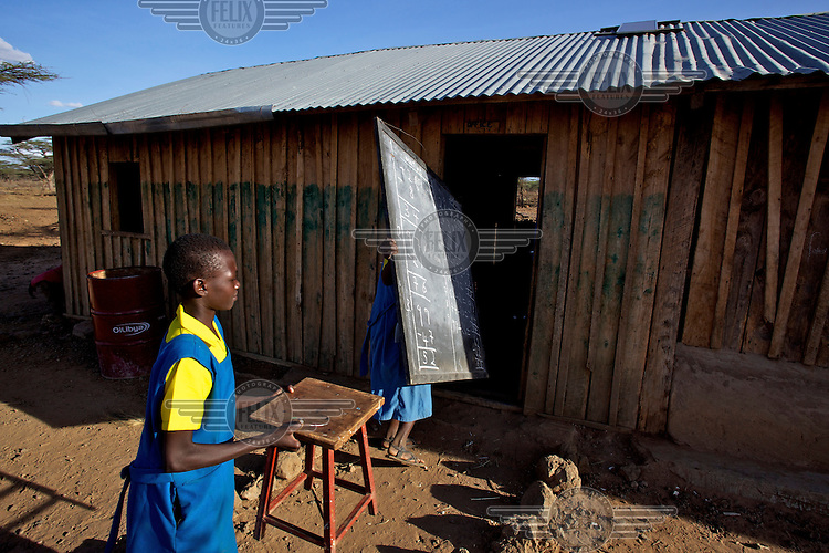 Ngaramara school students carry a black board and a chair back to a classrom in Isiolo, East Kenya.