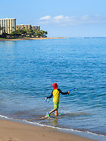 A boy with snorkel gear enters the water at Ka'anapali Beach, Maui.