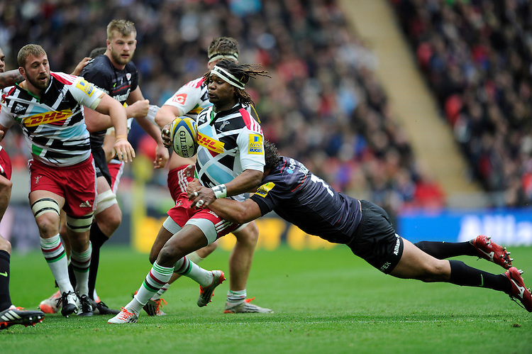 Marland Yarde of Harlequins is tackled by Jacques Burger of Saracens