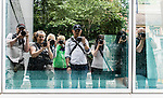 Photo walk group reflection in glass window of Dr Chau Chak Wing Business School Building at UTS.