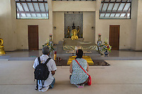 Borobudur, Java, Indonesia.  Mendut Buddhist Monastery. Visitors Praying in the Prayer Room for Visitors to Offer Homage to the Buddha.