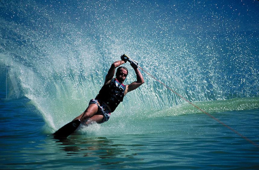 A waterskier lays over in a turn and sprays a wall of water. sports. Brad Bateman. Utah, Utah Lake.