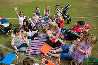 A group of mothers breastfeeding their babies and children sit on some grass and raise their hands to be counted as part of The Big Latch On annual awareness event in a park.
