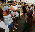Fisherman in Cartagena, Colombia haggles with locals over payment for helping to pull in his net.