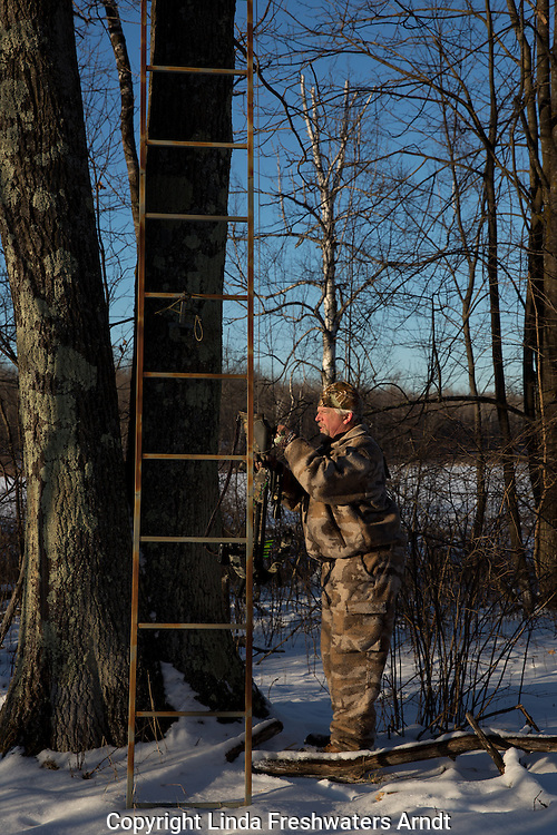 Hunter attaching crossbow to pull up rope