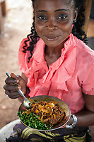 Nigeria. Enugu State. Enugu. A smiling Igbo woman eats cocoyam for lunch. Cocoyam is a common name for more than one tropical root crop and vegetable crop belonging to the Arum family (also known as Aroids and by the family name Araceae) and may refer to Taro (old cocoyam) or Malanga (new cocoyam. Cocoyams are herbaceous perennial plants belonging to the family Araceae and are grown primarily for their edible roots, although all parts of the plant are edible. Enugu is the capital of Enugu State, located in southeastern Nigeria.  2.07.19 © 2019 Didier Ruef