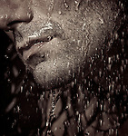 Closeup of a man unshaven chin with stubble and water running over it. Black and white sepia toned. Image © MaximImages, License at https://www.maximimages.com