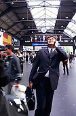 Zurich, Switzerland. Businessman in suit talking on a mobile phone; railway station.