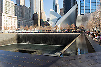 The North Pool of the National September 11 Memorial, with the Oculus World Trade Center Transportation Hub in the background in New York City.