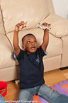 3 year old boy at home pretend play playing with toy animal tiger and zebra vocalizing vertical holding them high in air