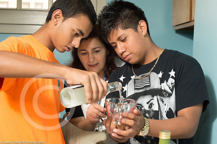 Education high school cooking elective taught by volunteers, female teacher working with two male students