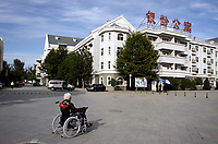 A woman sits inside the grounds of a retirement complex for the elderly.