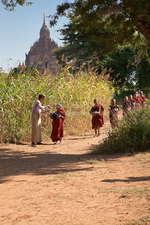 Myanmar, Burma. Bagan.  Woman Giving Rice to Young Novice Monks.