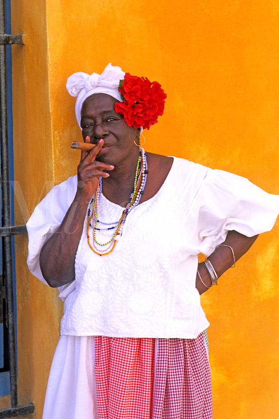 Native Cuban woman smoking a cigar while resting on a colorful yellow wall. Old Havana, Cuba