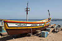 """Dakar, Senegal.  Fishing Boat on the Beach at Soumbedioune Fishing Village, now a part of the metropolis of Dakar.  The inscription on the left in Arabic reads """"Bismillah"""", """"In the name of God"""" often recited as an invocation of success or safety before undertaking an activity."""