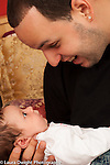 Father holds 1 month old newborn baby girl face to face interaction
