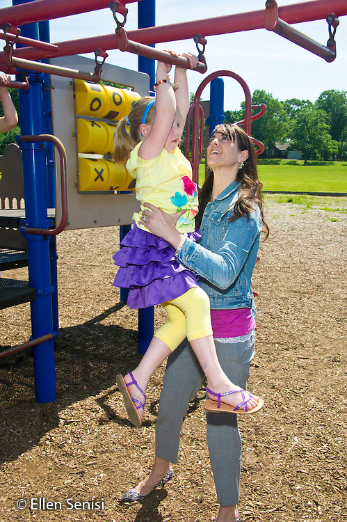 MR / Schenectady, NY. Zoller Elementary School. Kindergarten. Teacher helps student (girl, 5) who is learning how to cross the monkey bars at recess time on the playground. MR: San10, Les3. ID: AL-gKs. © Ellen B. Senisi