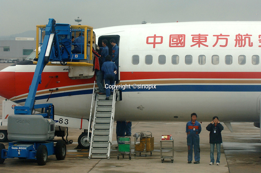 China Eastern planes are repaired by mechanics on the runway of Kunming Airport in Kunming, capital of Yunnan Province, west China...