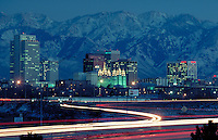 The Latter Day Saints (Mormon) Temple and skyline of Salt Lake City, Utah with Wasatch Mountains in the background at dusk with the city's lights on and automobile lights streaking by on the freeway. citycape, urban design. Salt Lake City Utah.