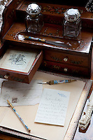 A letter of congratulations to Thomas Merthyr Guest on his engagement to Theodora lies open on a desk in the drawing room