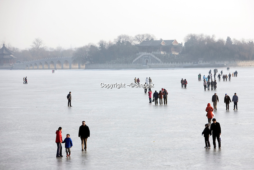 Tourists play on the ice at the Summer Palace. The Summer Palace, a palace 15km from Beijing, is mainly dominated by Longevity Hill (60 meters high) and Kunming Lake. It covers an expanse of 2.9 square kilometers, three quarters of which is water..Beijing. .Dec 2005