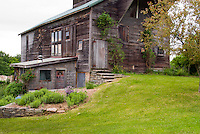 Pretty, large old barn set on top of a slope, with toolshed work building attached. . Board and batten door