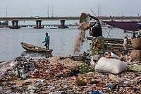 Mercato di Cotonou, una donna svuota un cesto, sullo sfondo una barca e un ponte