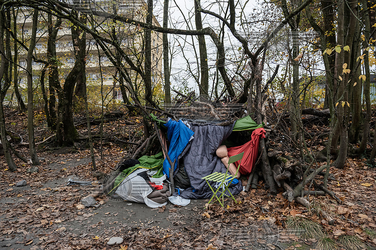 A homeless person's shelter beside the Avre River made with branches draped with old tents and sleeping bags and occupied by a teenage Morroccan boy.