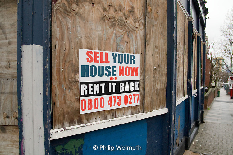 Estate agent's sign on a boarded-up shop in Woolwich