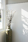 A tall vase of flowers sits by the window casting shadows across the white beaded board wall.