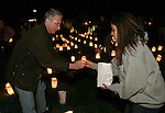 """SOUTHBURY, CT 01/01/08-010108BZ01- Ken Aspis, of Southbury, hands a lit candle to Lisamarie Farina, 19, of Southbury, while setting up luminaries to form the word """"HOPE"""" on the lawn outside Sacred Heart Church in Southbury Tuesday night.   The vigil was in remembrance of youth from the area who had untimely deaths recently.<br /> Jamison C. Bazinet Republican-American"""
