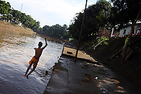 An Indonesian boy jumps into the Ciliwung River, a waterway that has been described as one of the most polluted rivers in the world. The river often floods, breaking its banks sending its polluted water into the nearby communities.
