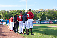 Billings Mustangs stand with their attention toward the flag during the National Anthem before a Pioneer League game against the Grand Junction Rockies at Dehler Park on August 15, 2019 in Billings, Montana. Billings defeated Grand Junction 11-2. (Zachary Lucy/Four Seam Images)