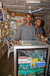 Two shopkeepers stand at the counter in a shop in Obollo-Afor, a junction town in Enugu state, Nigeria.  The display case sports a sticker advertising Confidence, a brand of family planning pills distributed in Nigeria by the Society for Family Health (SFH), Nigeria's largest non-governmental organization (NGO).