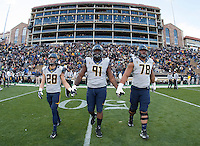 California captains' Jackson Bouza, Deandre Coleman, and Freddie Tagaloa walk on the field for coin toss before  the game against Colorado at Folsom Field in Boulder, Colorado on November 16th, 2013.  Colorado defeated California, 41-24.