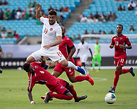 CHARLOTTE, NC - JUNE 23: Lucas Cavallini #19 leaps over defender Yosel Piedra #6 during a game between Cuba and Canada at Bank of America Stadium on June 23, 2019 in Charlotte, North Carolina.