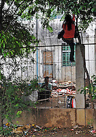 A Burmese lady climbs a flimsy border fence from Muse in Burma to Ruili at the Chinese - Burmese border crossing in Ruili, China. Chinese-Burmese gangs smuggle drugs across trhe border from Muse, in Burma and smuggle them out of Ruili using drug mules. Synthetic drugs are manufactured in labs in Burma and these dats form the bulk of drugs smuggled....PHOTO BY SINOPIX