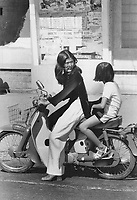 1972 FILE PHOTO -<br /> <br /> Traditional and mod blend on young lady on motorcycle; Square-heeled shoes and sunglasses are now popular in Saigon