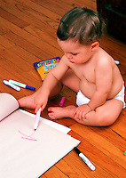 A toddler boy colors with markers on paper.