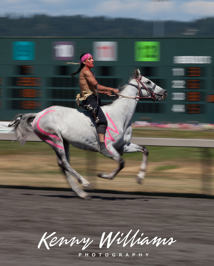 Ashton Old Elk riding white horse with warpaint, Battle of Horse Nation, Indian Horse Relay Racing, Emerald Downs, Auburn, Washington, WA, America, USA.